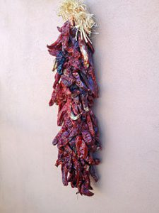Red chili peppers bundled and hanging to dry, by SteveStrummer (Own work) [CC0], via Wikimedia Commons