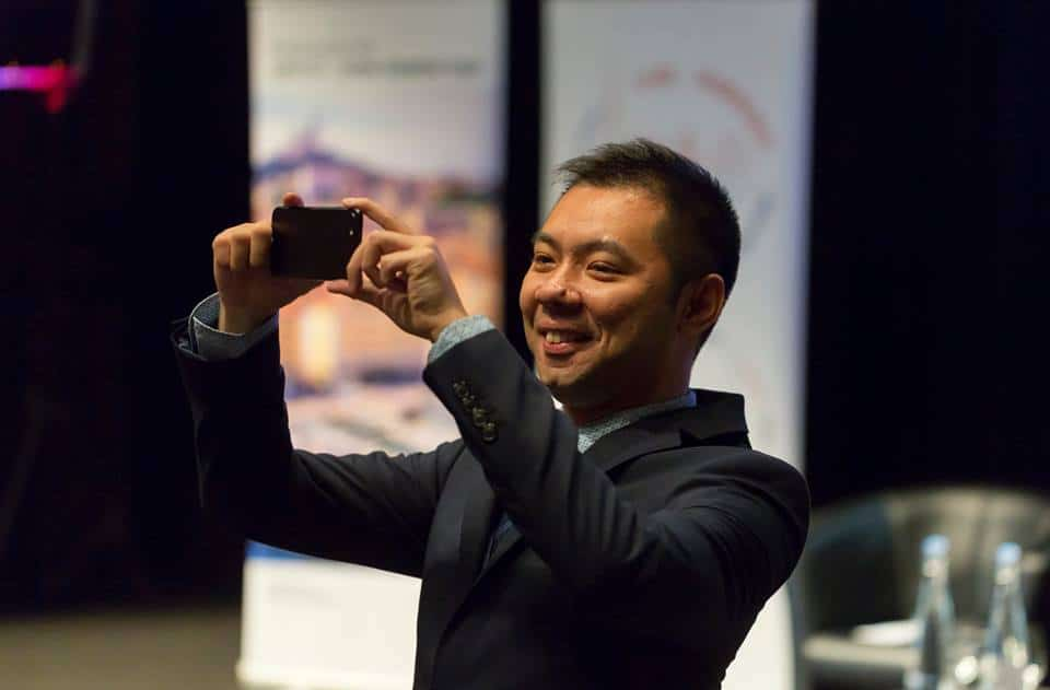 A speaker at the World Bridge Tourism taking a picture of the audience